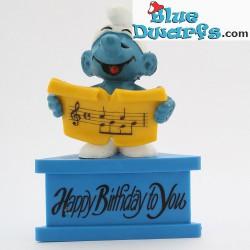 20038: Sänger Schlumpf mit Musikblatt  *Happy Birthday to you* (Podeste)